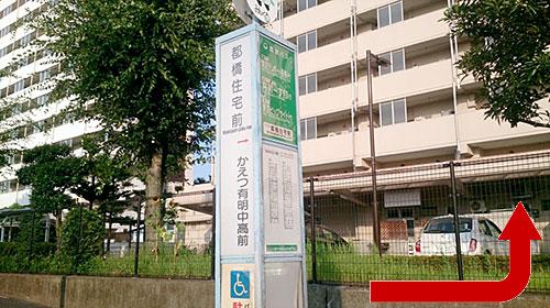 ①都橋住宅前バス停で下車後、バスの進行方向に進み、交差点を曲がります。